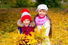 Deux petites filles en parc d'automne avec des feuilles Photos stock
