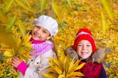 Deux petites filles en parc d'automne avec des feuilles Image libre de droits