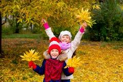 Deux petites filles en parc d'automne avec des feuilles Images stock