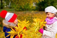 Deux petites filles en parc d'automne avec des feuilles Photo libre de droits