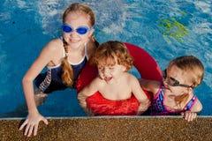 Deux petites filles et petit garçon jouant dans la piscine Photographie stock libre de droits