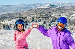 Deux petites filles faisant le coeur avec leurs mains dans la neige Images stock
