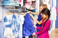 Deux petites filles font des emplettes ensemble dans le magasin de vêtements Image stock