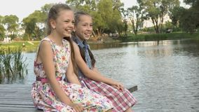 Deux petites filles gaies s'asseyent sur un pont en bois sur les banques de la rivière, rient et balancent leurs jambes un été banque de vidéos