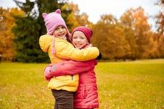 Deux petites filles heureuses étreignant en parc d'automne Image stock