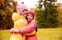 Deux petites filles heureuses étreignant en parc d'automne Images libres de droits
