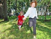 Deux petites filles heureuses attrapent des bulles de savon parmi des arbres Images stock