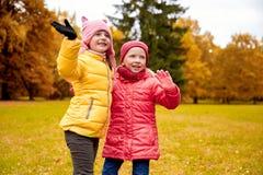 Deux petites filles heureuses ondulant la main en parc d'automne Photographie stock