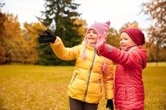 Deux petites filles heureuses ondulant la main en parc d'automne Photos stock
