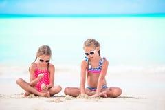 Deux petites filles heureuses ont beaucoup d'amusement à la plage tropicale jouant ainsi que le sable Images libres de droits