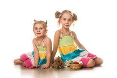 Deux petites filles jouant avec le lapin de Pâques sur un fond blanc Image stock