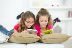 Deux petites filles jouant des jeux vidéo photographie stock