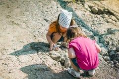 Deux petites filles jouent avec des pierres Images stock
