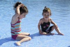 Deux petites filles jouent dans la piscine Photographie stock libre de droits