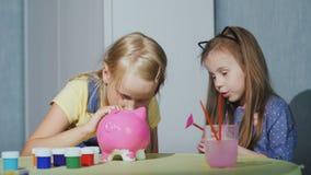 Deux petites filles jouent ensemble à la maison - pour peindre la tirelire banque de vidéos