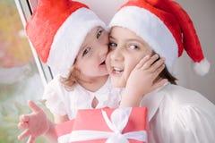Deux petites filles mignonnes avec des cadeaux de Noël Photographie stock libre de droits