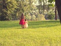 Deux petites filles mignonnes dans de belles robes ayant l'amusement au coucher du soleil toned Photos stock