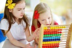 Deux petites filles mignonnes jouant avec l'abaque à la maison Grande soeur enseignant son enfant de mêmes parents à compter Images stock