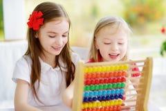 Deux petites filles mignonnes jouant avec l'abaque à la maison Grande soeur enseignant son enfant de mêmes parents à compter Photographie stock