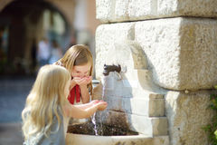 Deux petites filles mignonnes jouant avec une fontaine d'eau potable le jour chaud et ensoleillé d'été dans la ville de Desenzano Photographie stock