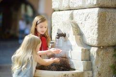Deux petites filles mignonnes jouant avec une fontaine d'eau potable le jour chaud et ensoleillé d'été dans la ville de Desenzano Photo libre de droits