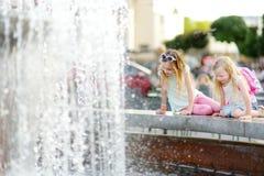Deux petites filles mignonnes jouant par la fontaine de ville le jour chaud et ensoleillé d'été Enfants ayant l'amusement avec de Photo libre de droits