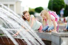 Deux petites filles mignonnes jouant par la fontaine de ville le jour chaud et ensoleillé d'été Enfants ayant l'amusement avec de Photos libres de droits