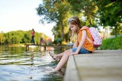 Deux petites filles mignonnes s'asseyant sur une plate-forme en bois par la rivière ou le lac Photographie stock