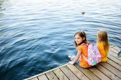 Deux petites filles mignonnes s'asseyant sur une plate-forme en bois par la rivière ou le lac Photos libres de droits