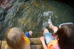 Deux petites filles mignonnes s'asseyant sur une plate-forme en bois par la rivière ou le lac Photographie stock libre de droits