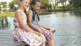 Deux petites filles mignonnes s'asseyent sur la berge sur un pont en bois au coucher du soleil une soirée d'été Portrait Fin vers banque de vidéos