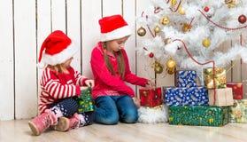 Deux petites filles ouvrent des cadeaux de Noël se reposant sur le plancher Photographie stock