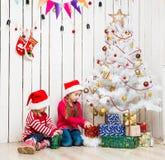 Deux petites filles ouvrent des cadeaux de Noël se reposant sur le plancher Photos libres de droits