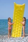 Deux petites filles restant sur la plage Photographie stock libre de droits