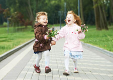 Deux petites filles riantes de gosses à l'extérieur Image libre de droits