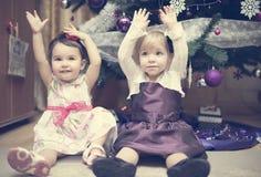 Deux petites filles s'asseyant près de l'arbre de Cristmas Photo stock