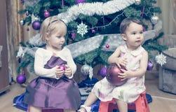 Deux petites filles s'asseyant près de l'arbre de Cristmas Images stock