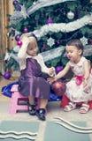 Deux petites filles s'asseyant près de l'arbre de Cristmas Photos stock