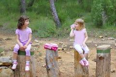 Deux petites filles s'asseyent sur des joncteurs réseau d'arbre de stationnement de forêt Images libres de droits