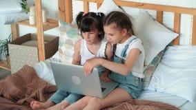 Deux petites filles s'asseyent sur le lit, ordinateur portable ouvert pour voir des bandes dessinées, mouvement lent banque de vidéos