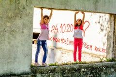 Deux petites filles se tenant sur la vieille ouverture de fenêtre images stock