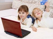 Deux petites filles sont avec un ordinateur portatif Images stock