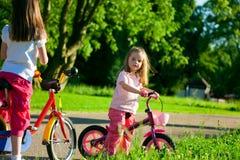 Deux petites filles sur des bicyclettes Image stock