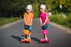 Deux petites filles sur des scooters Photographie stock libre de droits