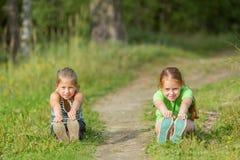 Deux petites filles vont chercher la poignée sur l'allée verte nature Photos stock