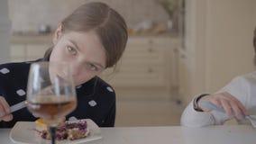 Deux petites jolies filles s'asseyant à la table mangeant un gâteau délicieux banque de vidéos