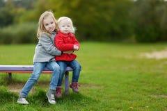 Deux petites soeurs étreignant sur un banc Image stock