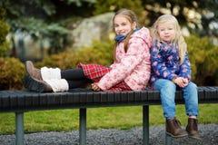 Deux petites soeurs adorables étreignant et caressant dehors la belle journée de printemps Photos stock