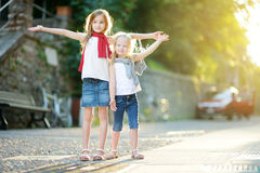 Deux petites soeurs adorables ayant l'amusement ensemble la soirée chaude et ensoleillée d'été dans la ville de Desenzano del Gar Image stock