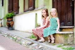 Deux petites soeurs adorables ayant l'amusement sur la rue célèbre de Literatu à Vilnius Image stock